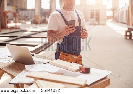 Male Builder Using Mobile Phone At Construction Site