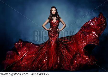 Brunette Model In Red Long Shining Dress. Elegant Beautiful Woman In Luxury Gown Over Fantasy Blue N