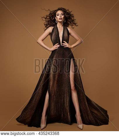 High Fashion Model In Black Dress With Golden Glitters Over Beige. Luxury Brunette Woman In Sexy Eve