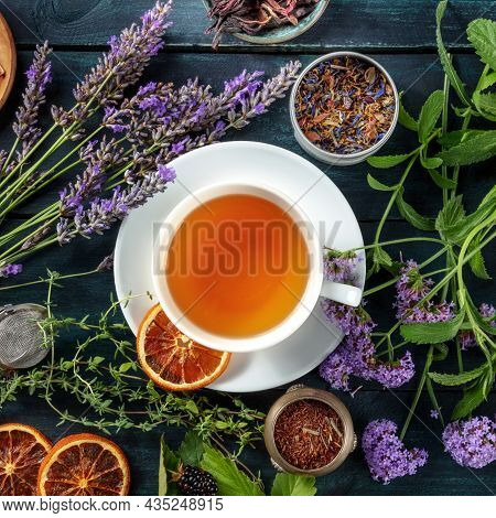 Tea, Overhead Square Shot. Herbs, Flowers And Fruit Around A Cup Of Tea On A Dark Rustic Wooden Back