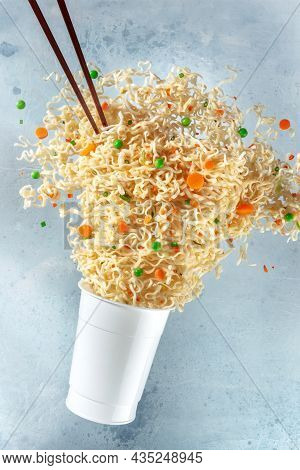 Ramen Cup With Noodles Floating Out Of It And Chopsticks, Fast Food Levitation. Instant Noodle Meal