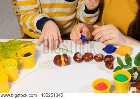 Mother And Son Sculpt Autumn Craft Caterpillar From Chestnuts And Plasticine