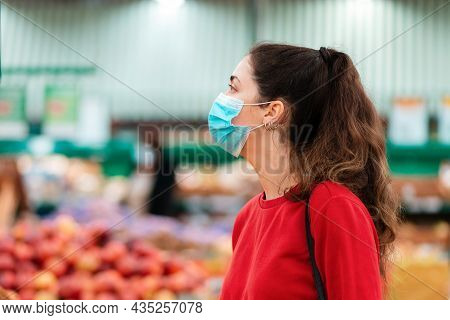 Shopping During The Coronavirus Pandemic. Portrait Of A Young Woman In A Medical Mask On Her Face Lo