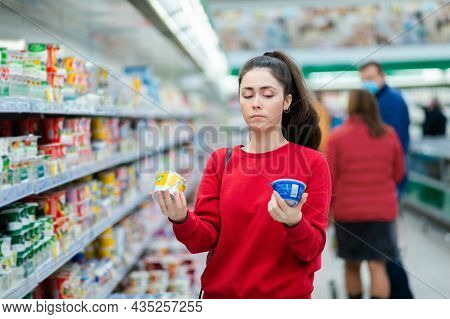 A Young Caucasian Woman Stands In A Supermarket And Thoughtfully Chooses Between Two Yogurts. Indoor