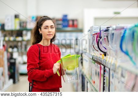 Portrait Of Young Woman Holding A Light Green Carafe With A Water Filter In A Store. The Concept Of