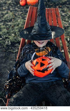 Halloween Kids. A Cute Little Boy, A Kid Wearing A Witch Hat With An Orange Jack O Lantern Bucket Of