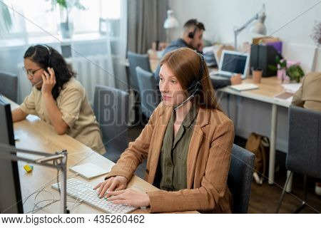 Young female operator of call center consulting clients in front of computer against co-workers