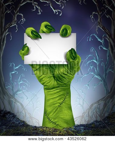 Zombie rising hand holding a blank sign card as a spooky halloween or scary symbol with textured green skin and monster fingers with stitches in a foggy night time tree forest background as a cemetary like creepy place. poster