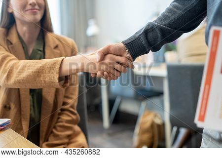 Handshake of two young successful office workers against workplace