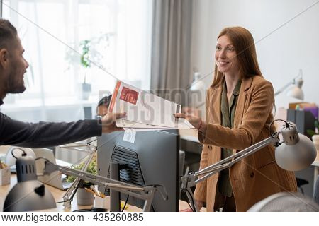 Young smiling businesswoman passing financial papers to male colleague over computer monitor