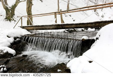 pedestrian wooden bridge over mountain stream in winter Carpathians during snowfall, Ukraine
