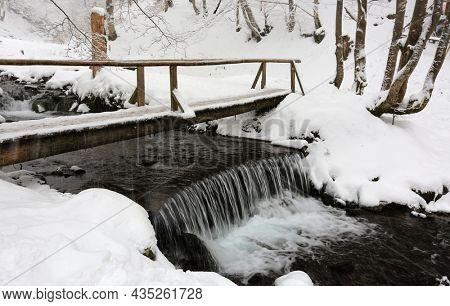 Snowfall over wooden bridge in winter forest. Take it in Ukrainian Carpathian mountains