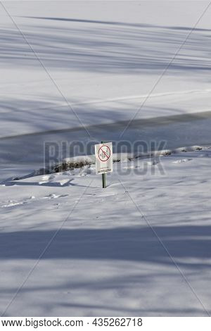 Winter River Covered With Snow And Ice And A Prohibiting Sign