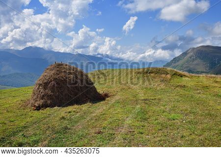 Stack Of Hay. Caucasus Alpine Meadow And Mountains Landscape In Chechnya, Russia. Vedeno District Of