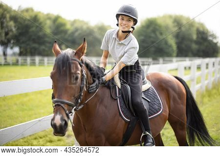 Female Horseman Riding Brown Thoroughbred Horse On Green Meadow Near Fence In Countryside. Concept O