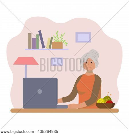 An Elderly Woman At A Laptop. Grandma Is At The Computer.  An Old Lady Is Sitting At A Table With A