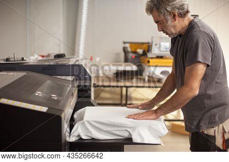 Professional Graphic Print Technician Work On Digital T-shirt Printing Heat Press Machine In Printin
