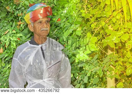 Close-up Portrait Of An Indian Farmer Stands In The Garden With A Colored Turban Tied On His Head As