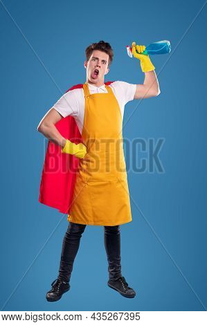 Full Body Of Crazy Young Male In Yellow Apron And Red Superhero Cloak Holding Bottle, With Detergent
