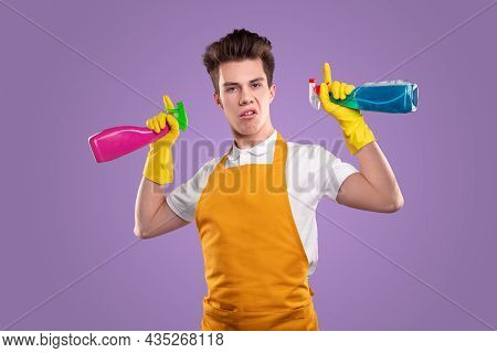 Funny Proud Young Man In Apron And Gloves Holding Colorful Bottles With Detergents, And Pointing Up
