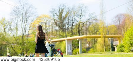 Back view of girl on bicycle wearing on black short dress. Young Woman riding along road on green spring  outdoor Park. Sporty young girl riding a bicycle on a sunny morning, view from the back