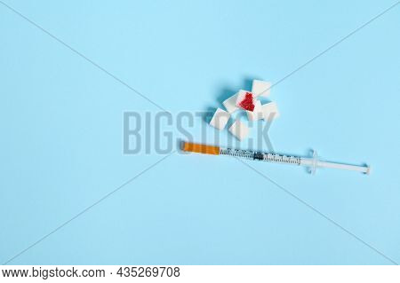 Flat Lay Of Insulin Syringe And Pure Refined White Sugar Cubes With Blood Drop Isolated Over Colored