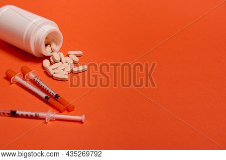 Studio Shot Of Insulin Syringes And Pharmaceutical Pills Scattered From A White Medicament Container