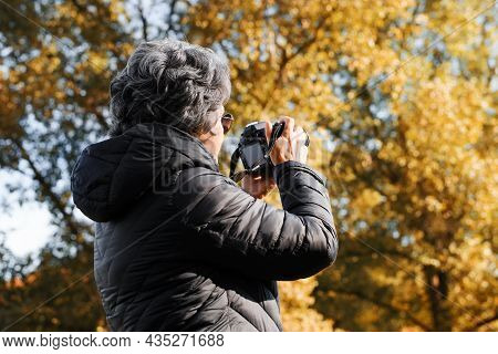 Back View Of Senior Woman Photographer Using Digital Camera Photographing Autumn Landscape In Nature
