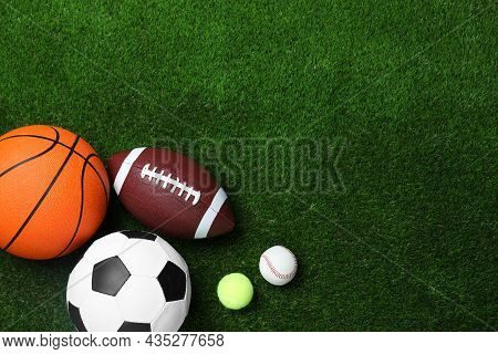 Set Of Different Sport Balls On Green Grass, Flat Lay. Space For Text