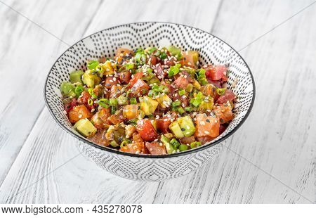 Bowl Of Tuna And Salmon Poke On The Wooden Table