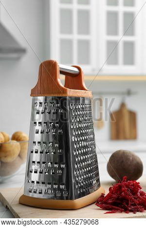 Grater And Fresh Ripe Beetroot On Table In Kitchen