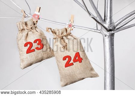 Two Matting Bags For Gifts With Numbers 23 And 24 Hanging On Silver Tree. 23, 24 - Advent Calendar.