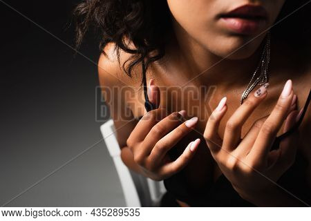 Cropped View Of Seductive African American Woman Adjusting Straps On Crop Top While Posing On Black