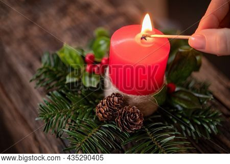 Close up of woman hand lighting red festive candle with matchstick. High angle view of woman lighting advent candle kept over xmas wreath on wooden table. Top view of girl hands burning candle.