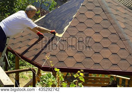 The Roofer Prepares The Surface For Fixing The Tiles, Marks The Screws On The Wooden Surface