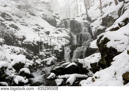 landscape with a waterfall in the winter mountain forest during a snowfall. Take it in Carpathian mountains, Ukraine