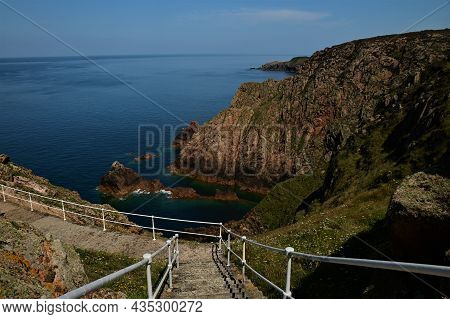 A View Along The Rugged Coastline And Deep Blue Waters At Grosnez On The Channel Island Of Jersey