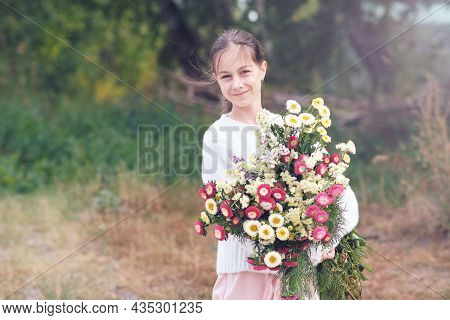 A Girl Holds In Her Hands A Large Beautiful Bouquet Of Autumn Flowers In A White Sweater In A Forest