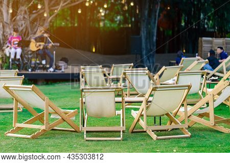 Many White Deck Chairs With Tables For Dinner In Lawn Is Surrounded By Shady Green Grass With Blurre