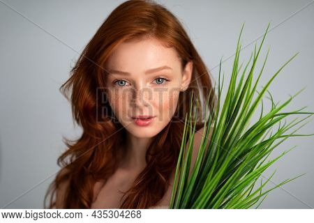 Red-haired Young Lady Posing With Green Grass Plant, Gray Background