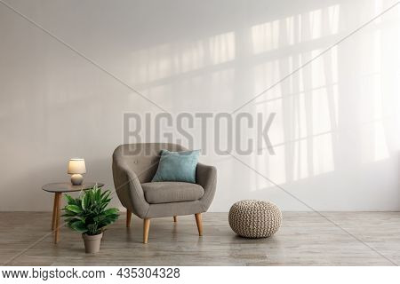 Comfortable Armchair With Pillow, Luminous Lamp On Table, Potted Plant And Ottoman On Floor On Gray