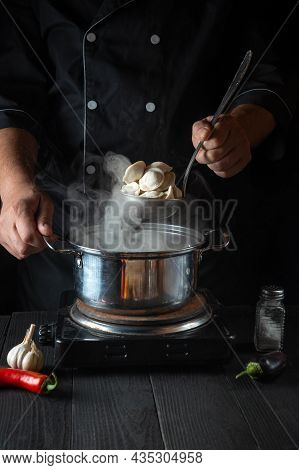 Professional Chef Cooks Meat Dumplings In A Saucepan In The Restaurant Kitchen. Close-up Of The Hand