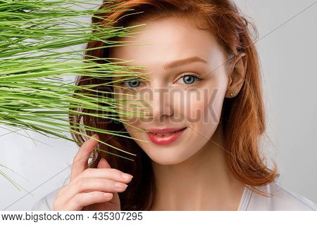 Ginger-haired Girl Posing With Green Grass Near Face, Gray Background