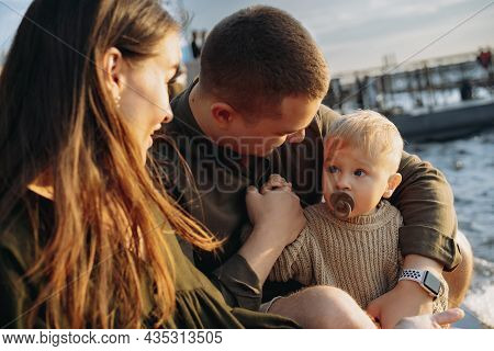 Family. Mom, Dad And Baby Boy Sitting At The Quay, Parents Looking At Son Sucking A Dummy. Image Wit