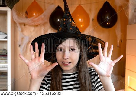 Little Pretty Girl Witch In Black Wizard Hat Says Boo With Scary Gesture. Halloween Kids Portrait. G