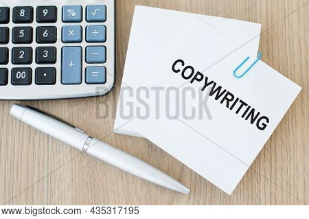 A Card With Text Copywriting Affixed On A Paper Clip To Other Note Cards On A Wooden Table With A Co