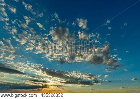Yellow Rays Of The Setting Sun Shine In A Cloud Gap Low Above The Horizon And Illuminate A Scatterin