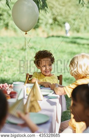 Diverse Group Of Kids At Picnic Table Outdoors Decorated With Balloons For Birthday Party In Summer
