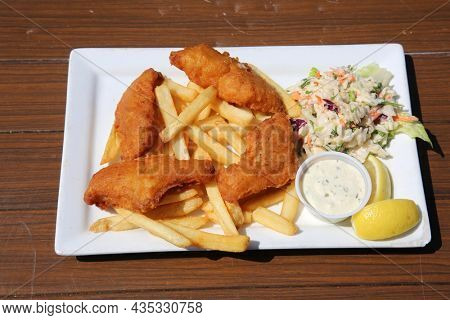Fish and chips with lemon wedges. Gourmet fish and chips garnished with parsley flakes and served with side salad. British fish and chips. Fried Cod and French Fries. Cod Fish and Chips.