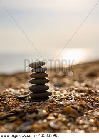 Stable Pebble Tower On The Beach At Sunset. Vertical Format. The Concept Of Balance And Tranquility.